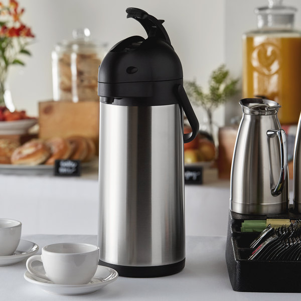 Stainless steel airpot beside coffee cup