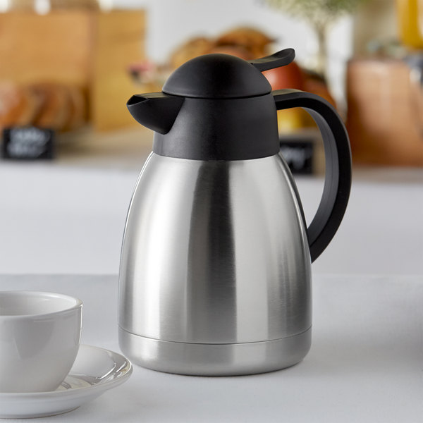 Insulated thermal coffee carafe sitting next to coffee cup