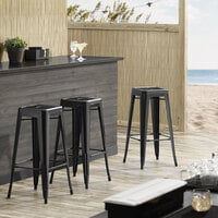 Lancaster Table & Seating Alloy Series Black Stackable Metal Indoor / Outdoor Industrial Barstool with Drain Hole Seat