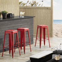 Lancaster Table & Seating Alloy Series Distressed Red Stackable Metal Indoor / Outdoor Industrial Barstool with Drain Hole Seat