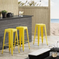 Lancaster Table & Seating Alloy Series Yellow Stackable Metal Indoor / Outdoor Industrial Barstool with Drain Hole Seat