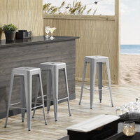 Lancaster Table & Seating Alloy Series Silver Stackable Metal Indoor / Outdoor Industrial Barstool with Drain Hole Seat