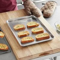 Baker's Mark Heavy-Duty Half Size 16 Gauge 13 inch x 18 inch Wire in Rim Aluminum Perforated Bun / Sheet Pan